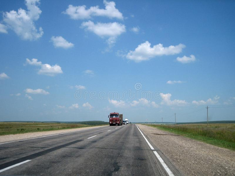 La carretera del coche en las grietas entra lejos la distancia en un día soleado brillante imagenes de archivo