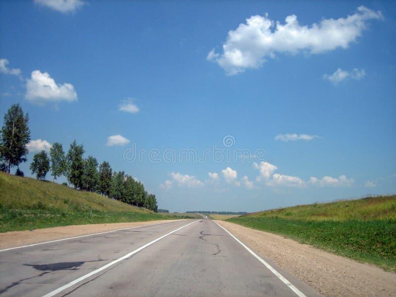 La carretera del coche en las grietas entra lejos la distancia en un día soleado brillante imagen de archivo libre de regalías