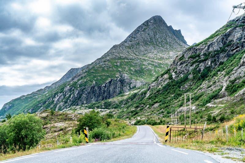La carretera en las montañas noruegas, el día del verano, nubes justo encima de las cumbres La línea eléctrica desde el lado dere foto de archivo libre de regalías