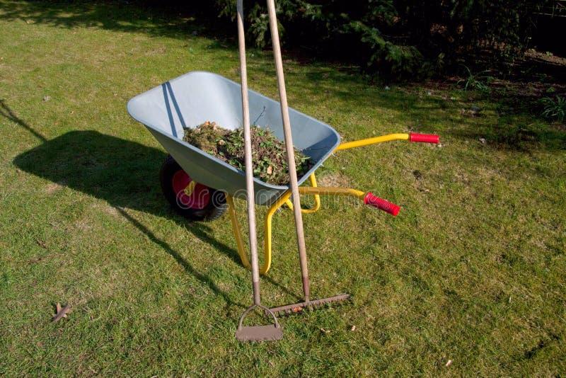 La carretilla de rueda en la hierba en el jardín con el rastrillo y la azada delante de la mitad romántica enmaderó la casa con e imágenes de archivo libres de regalías