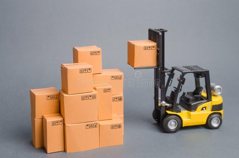 La carretilla elevadora amarilla aumenta una caja de cartón al top de una pila de la pila de cajas Warehouse, acción comercio, al imágenes de archivo libres de regalías