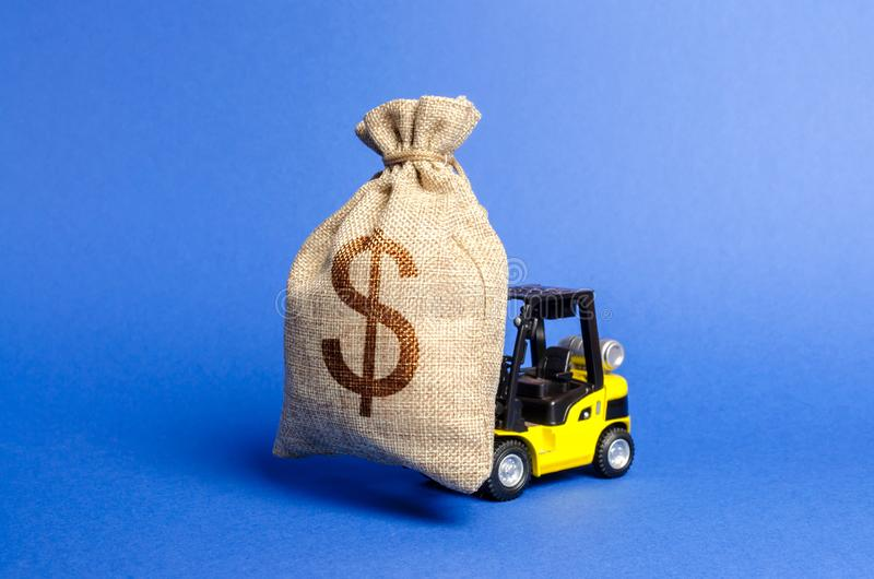 La carretilla elevadora amarilla lleva un bolso grande del dinero Atracción de la inversión en el desarrollo y la modernización d imagen de archivo libre de regalías