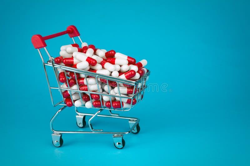 La carretilla que hac?a compras llen? c?psulas medicinales rojas imagen de archivo libre de regalías