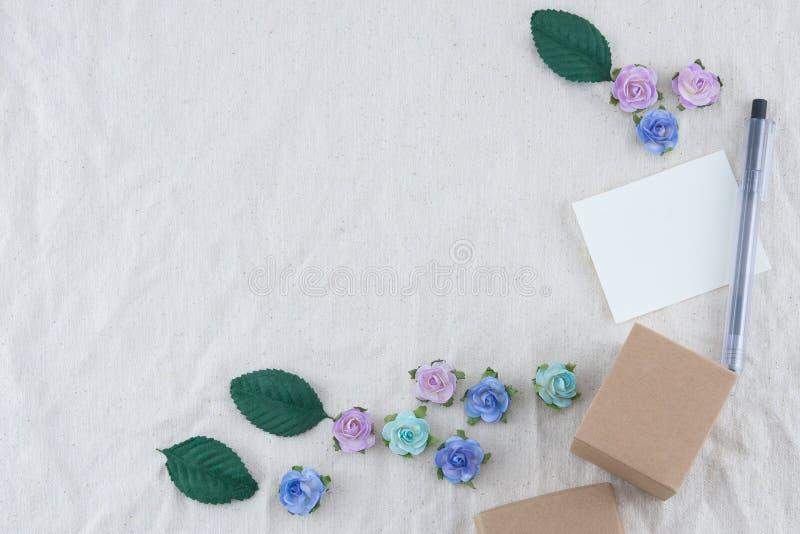 La carta in bianco bianca, la penna ed il contenitore di regalo marrone decorano con i fiori di carta del tono blu fotografia stock libera da diritti