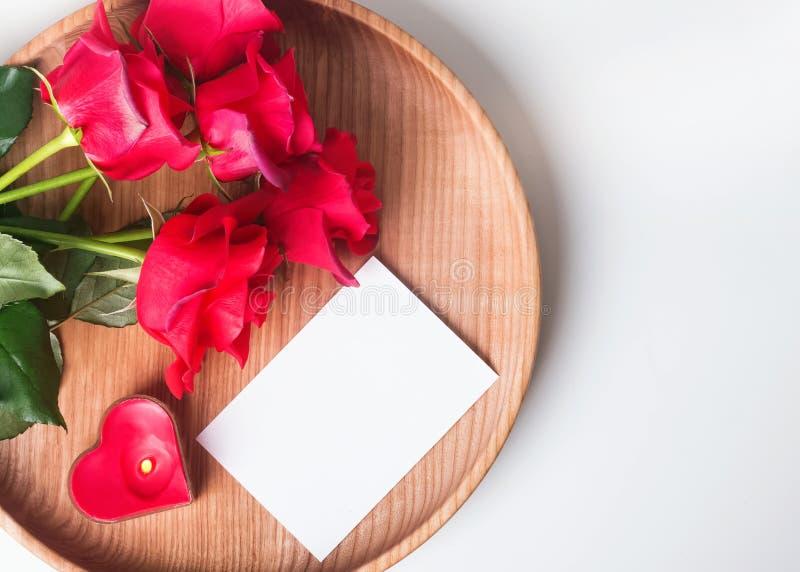 La carta in bianco, le rose rosse ed il cuore hanno modellato la candela nel di legno plat fotografia stock libera da diritti