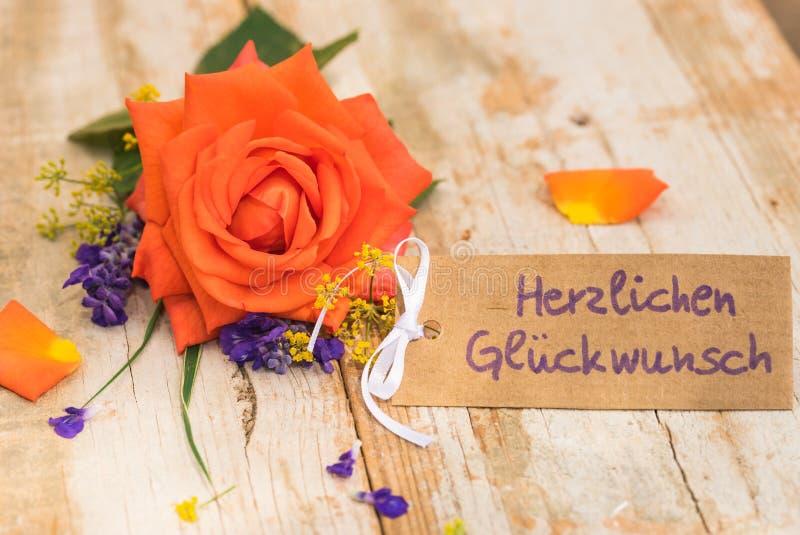 La carta con testo tedesco, Herzlichen Glueckwunsch, la congratulazione di mezzi e la rosa arancione fioriscono fotografia stock libera da diritti