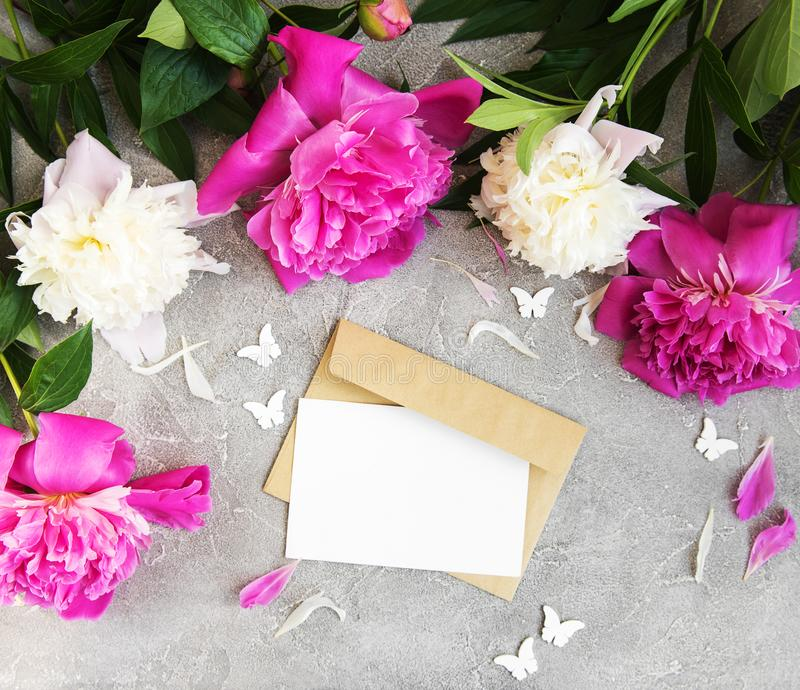La carta dell'invito, la busta del mestiere e la peonia rosa fiorisce immagine stock