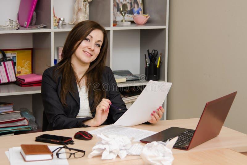 La carta della tenuta della ragazza di affari esamina la struttura e sorridere fotografia stock libera da diritti