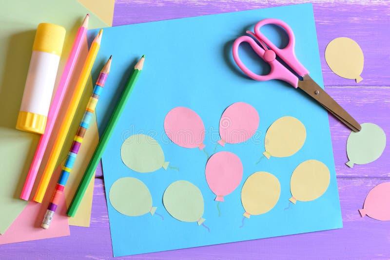 La carte avec les ballons à air de papier, ciseaux, bâton de colle, papier coloré, crayonne sur une table Enseignant badine pour  photo stock