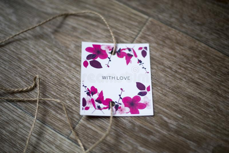 """La carte avec les fleurons et l'inscription """"avec amour """", se trouve dans la perspective de, attaché par une corde photo stock"""