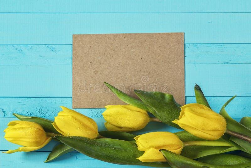 La carte brune vierge avec les tulipes jaunes sur le bleu a peint la planche en bois photographie stock