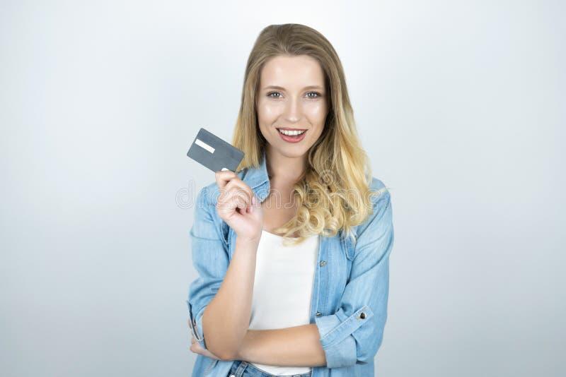 La carte de banque blonde de participation de jeune femme semble le fond blanc heureux photo stock