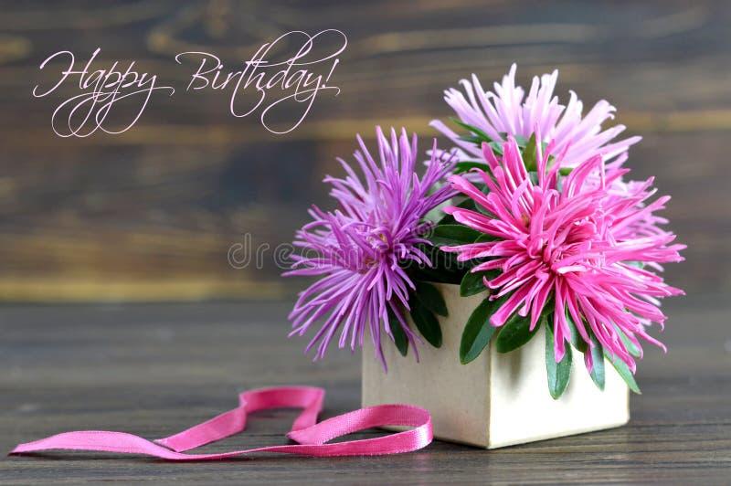 La carte de joyeux anniversaire avec des fleurs a arrangé dans le boîte-cadeau images stock