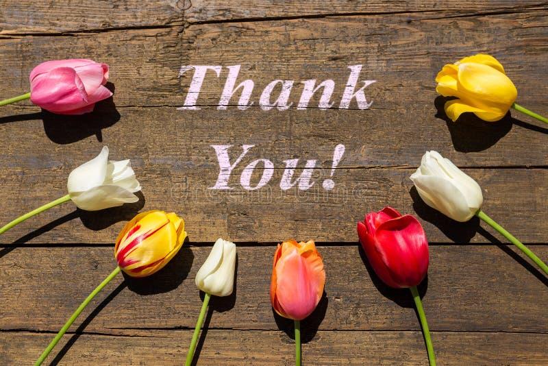 La carte de voeux avec des tulipes sur la table en bois avec des mots vous remercient photographie stock libre de droits