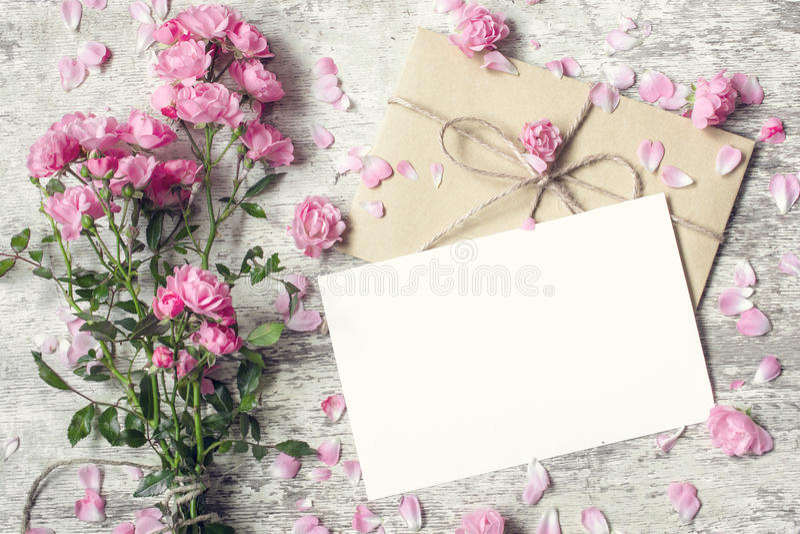 La carte de voeux et l'enveloppe blanches vides avec la rose de rose fleurit photographie stock libre de droits