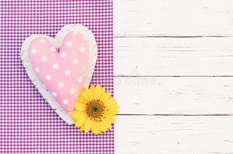 La carte de voeux romantique avec le coeur rose et la fleur jaune fleurissent photo libre de droits
