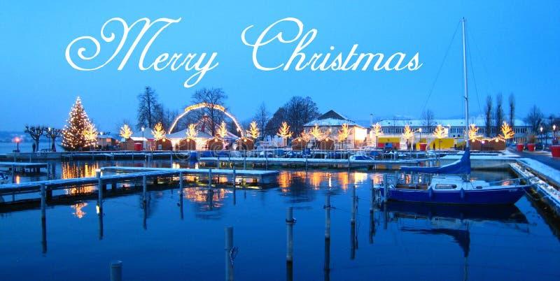 La carte postale avec un beau marché suisse de Noël de la Suisse sur le rivage de lac avec la neige a couvert des bateaux à l'heu illustration de vecteur