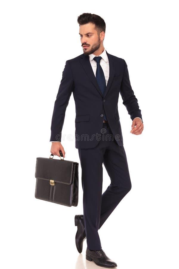 La cartera que lleva joven del hombre de negocios está caminando y mira detrás imagenes de archivo