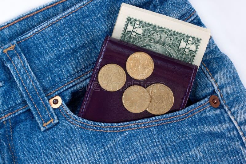 La cartera y el dinero listo están mintiendo en el bolsillo lateral de tejanos fotografía de archivo libre de regalías