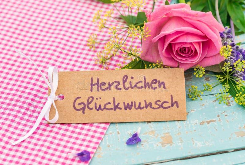 La cartolina d'auguri con testo tedesco, Herzlichen Glueckwunsch, significa la congratulazione con il mazzo di fiori fotografia stock libera da diritti