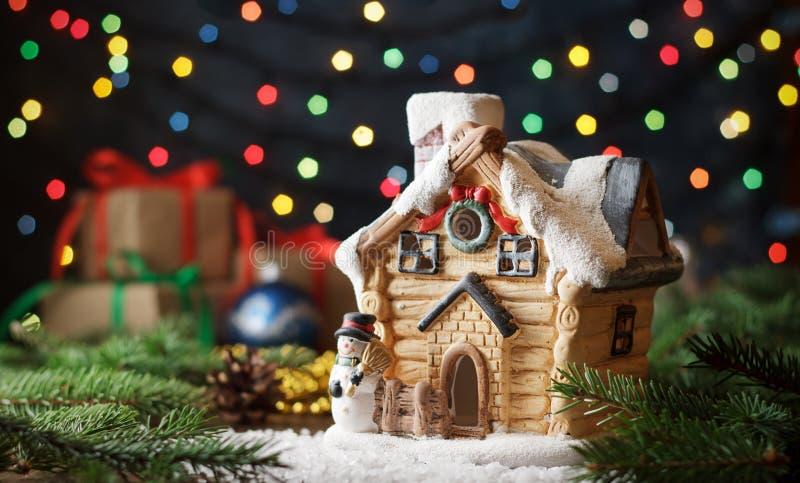 La cartolina di Natale con la casa decorativa del giocattolo con il pino si ramifica, regali sul fondo del bokeh della ghirlanda immagine stock libera da diritti