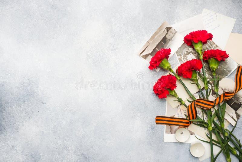 La cartolina può 9 - foto rosse di George Old del nastro dei garofani su un fondo concreto Simbolo della vittoria nella grande gu fotografia stock