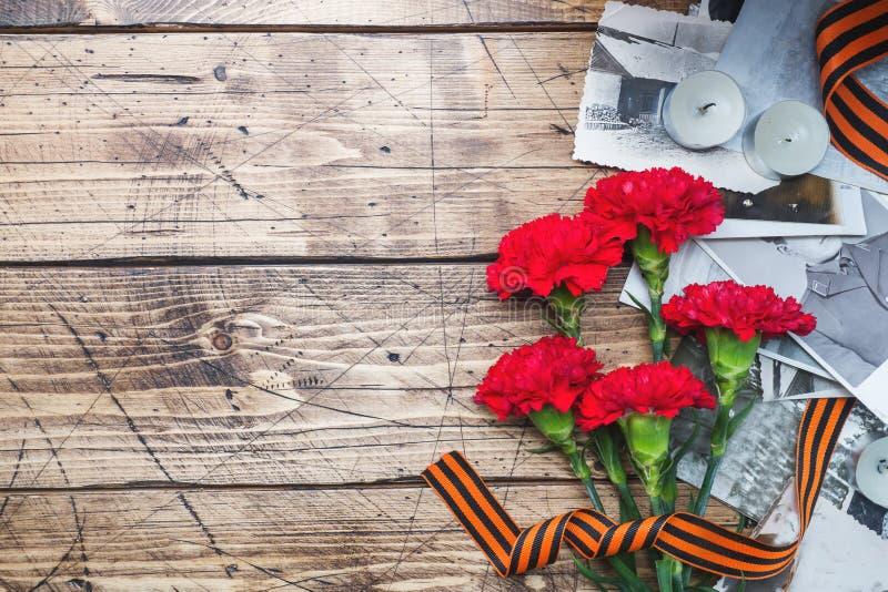 La cartolina pu? 9 - foto rosse di George Old del nastro dei garofani su un fondo di legno Simbolo della vittoria nella grande gu fotografie stock