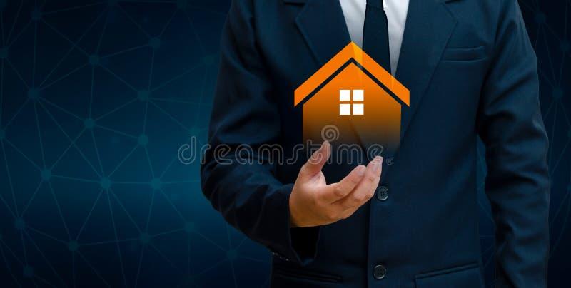 La casa è nelle mani dell'icona della casa dell'uomo di affari o del concetto di simbolo delle applicazioni e del futuro della ca immagini stock