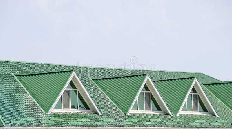 La casa con le finestre di plastica e un tetto verde dello strato ondulato Tetto verde del profilo ondulato del metallo e delle f fotografia stock libera da diritti