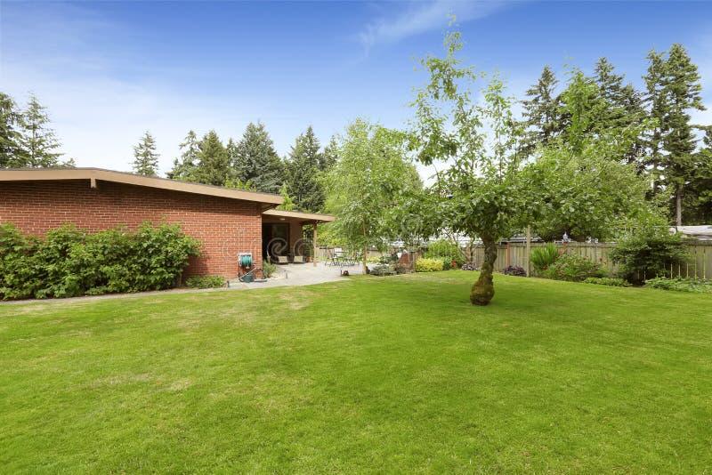 La casa con mattoni a vista esteriore con il paesaggio del cortile e del patio progetta fotografia stock libera da diritti