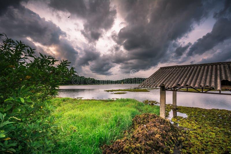La casa de bomba vieja y el cielo dramático en el lago Cheloor es, Sasthamcotta fotos de archivo