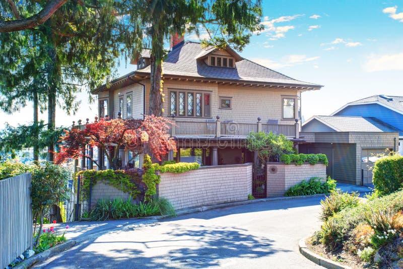 La casa de dos pisos beige con el tejado de teja y el encintado hermoso apelan foto de archivo - La casa en el tejado ...