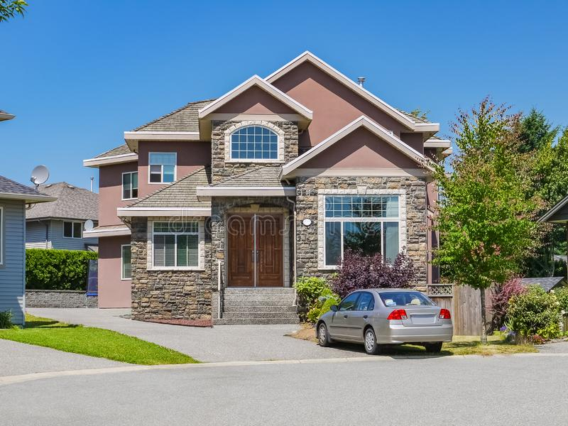 La casa de lujo de la familia con un coche parqueó en la calzada Casa residencial el día soleado en fondo del cielo azul fotografía de archivo