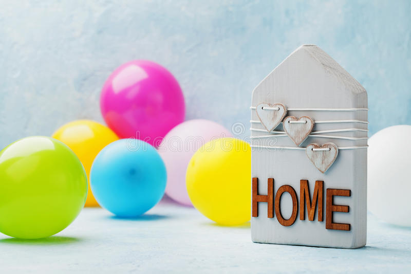 La casa de madera adornó corazones y los balones de aire en fondo azul Partido del estreno de una casa, regalo, propiedades inmob fotografía de archivo libre de regalías