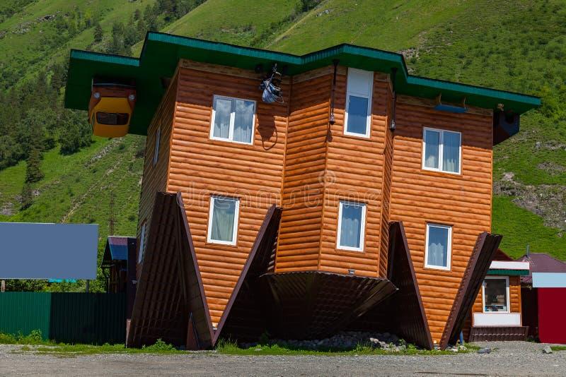 La casa de madera vieja dio vuelta al revés para el entretenimiento como atracción en las montañas de Altai en el fondo imagenes de archivo