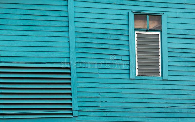 La casa de madera vieja pintó el azul brillante con la ventana de cristal fotografía de archivo