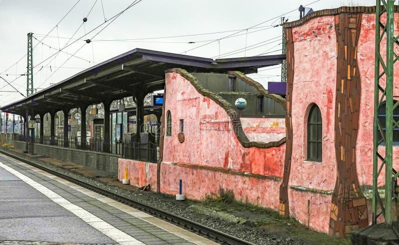 La casa del custode ferroviario rosso e color carne all'estremità di una piattaforma in Uelzen fotografia stock