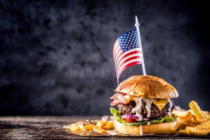 La casa del primo piano ha prodotto l'hamburger del manzo con la bandiera americana e le fritture su w fotografia stock