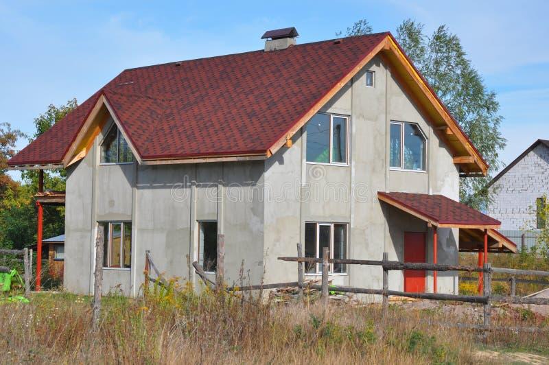 La casa della costruzione con asfalto copre le pareti dello stucco e del tetto Costruzione del tetto con le assicelle dell'asfalt fotografia stock libera da diritti