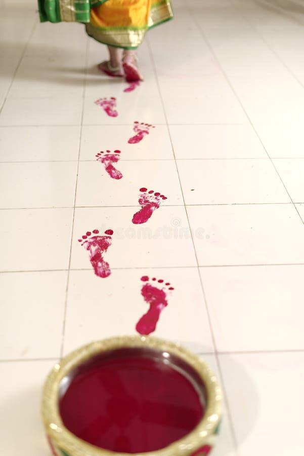 La casa dello sposo entrante della sposa indù indiana dopo nozze con i suoi segni del piede in pasta rossa di kum di kum. immagini stock libere da diritti