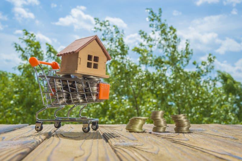 La casa di legno su un carrello con soldi conia Contro lo sfondo degli alberi e del cielo verdi immagine stock