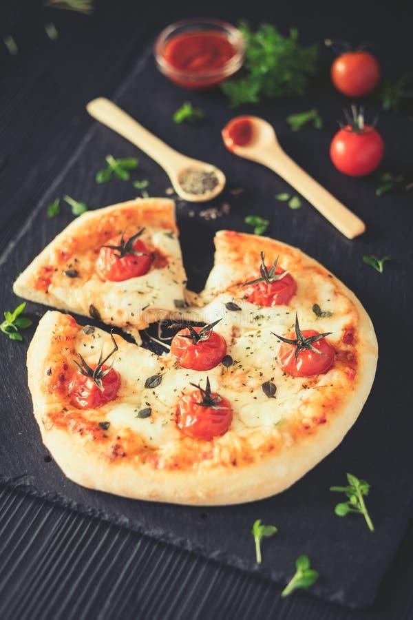 La casa di Margherita ha prodotto la pizza Vista superiore sulla tavola scura fotografie stock