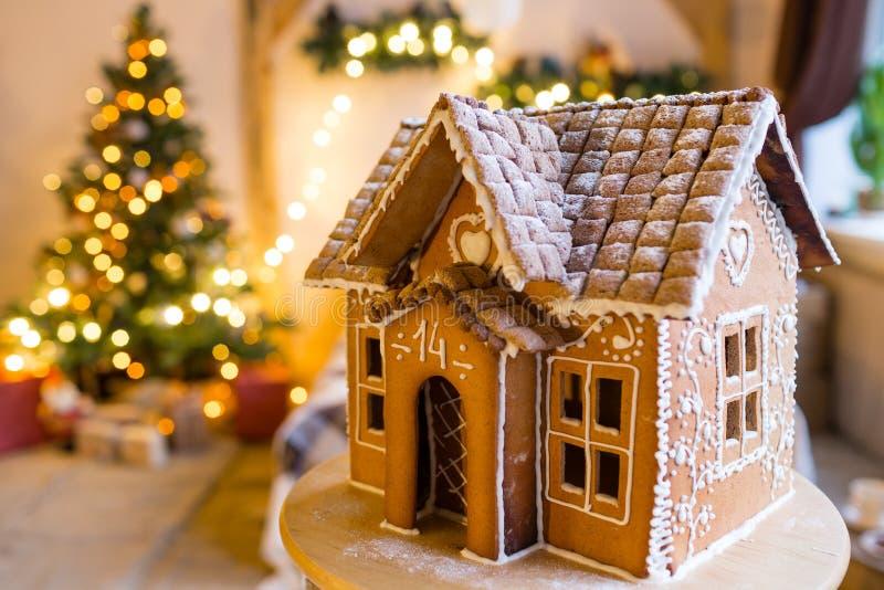 La casa di pan di zenzero sopra le luci defocused di Chrismtas ha decorato l'albero di abete fotografia stock