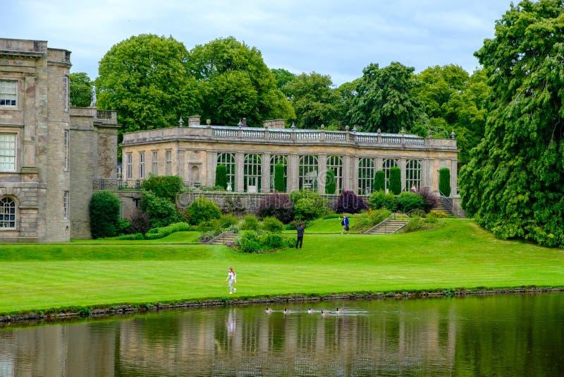 La casa e il parco a Cheshire della Lyme Hall storico inglese dello Stato con una ragazza che cammina e delle oche da nuoto in vi immagini stock libere da diritti