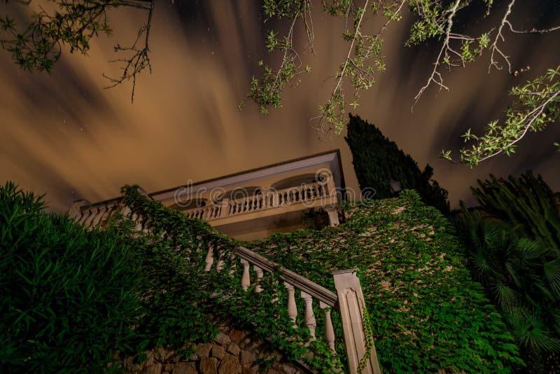 La casa española debajo del cielo nocturno nublado foto de archivo libre de regalías