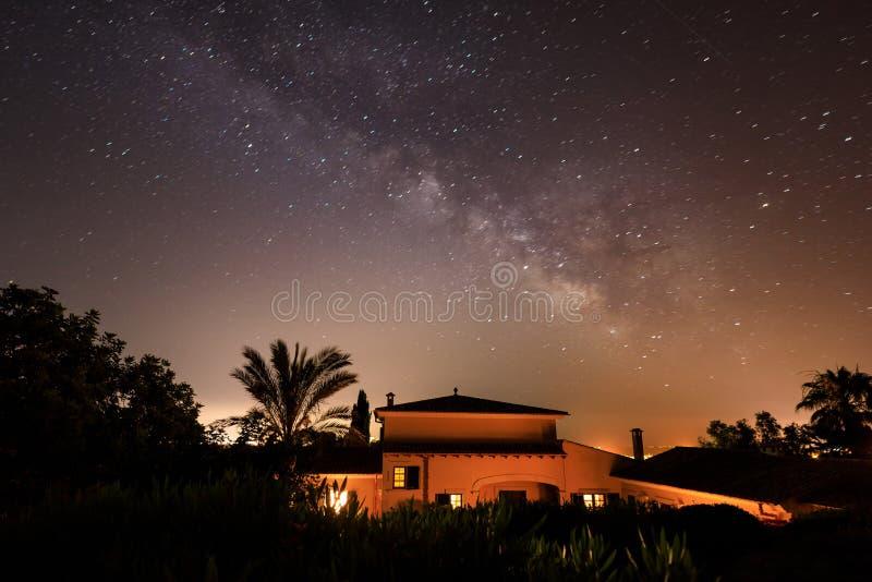 La casa española debajo del cielo nocturno nublado fotografía de archivo