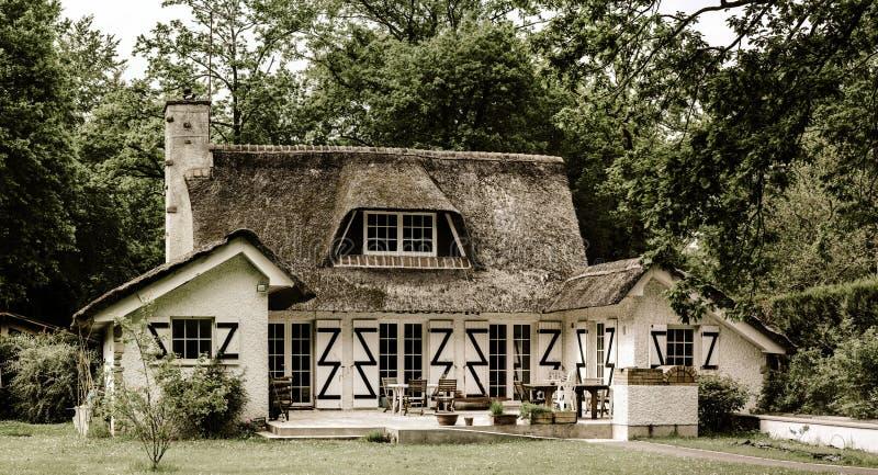 La casa francese tipica della campagna con ricopre di paglia il tetto fotografia stock