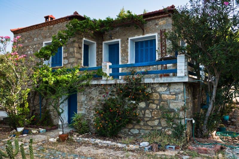 La casa greca fatta tradizionalmente della pietra con blu e bianco ha colorato le finestre in Sithonia immagine stock libera da diritti