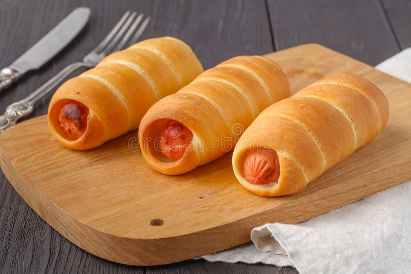 La casa ha fatto i maiali in una coperta Le salsiccie hanno arrivato a fiumi la pasta del croissant, cotta immagine stock