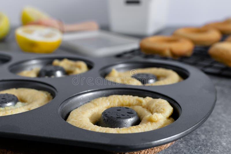 La casa ha fatto il concetto bollente, pasta della ciambella, guarnizioni di gomma piuma, uova, limone, utensili della cucina immagini stock